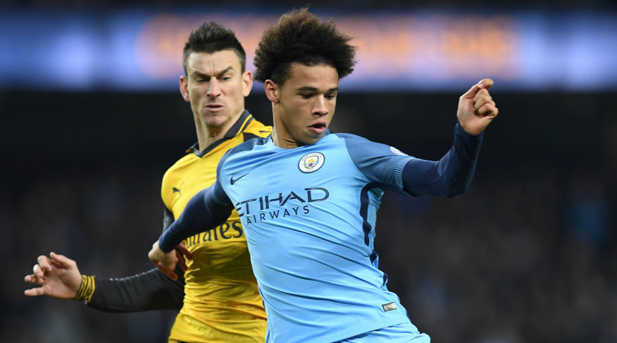 Manchester City's German midfielder Leroy Sane shoots the score their first goal during the English Premier League football match between Manchester City and Arsenal at the Etihad Stadium in Manchester, north west England, on December 18, 2016. / AFP / Paul ELLIS / RESTRICTED TO EDITORIAL USE. No use with unauthorized audio, video, data, fixture lists, club/league logos or 'live' services. Online in-match use limited to 75 images, no video emulation. No use in betting, games or single club/league/player publications.  /         (Photo credit should read PAUL ELLIS/AFP/Getty Images)